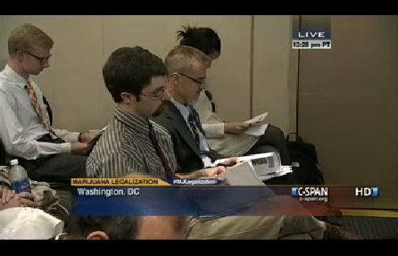"The author, featured in a screen capture of C-SPAN coverage of the Brookings Institution event called, ""The Politics of Marijuana Legalization."" To the author's left, John Walsh of the Washington Office on Latin America."